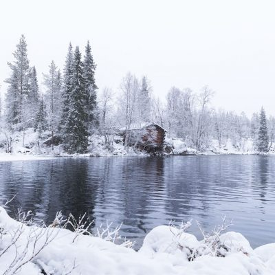 A small cabin along a wild river in Finnish Lapland during winter