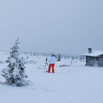 Snowshoeing between cabins and pines is a great way to explore Finnish Lapland
