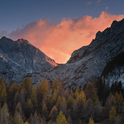 The sun setting behind the moutain range in Dolomites and litting up clouds