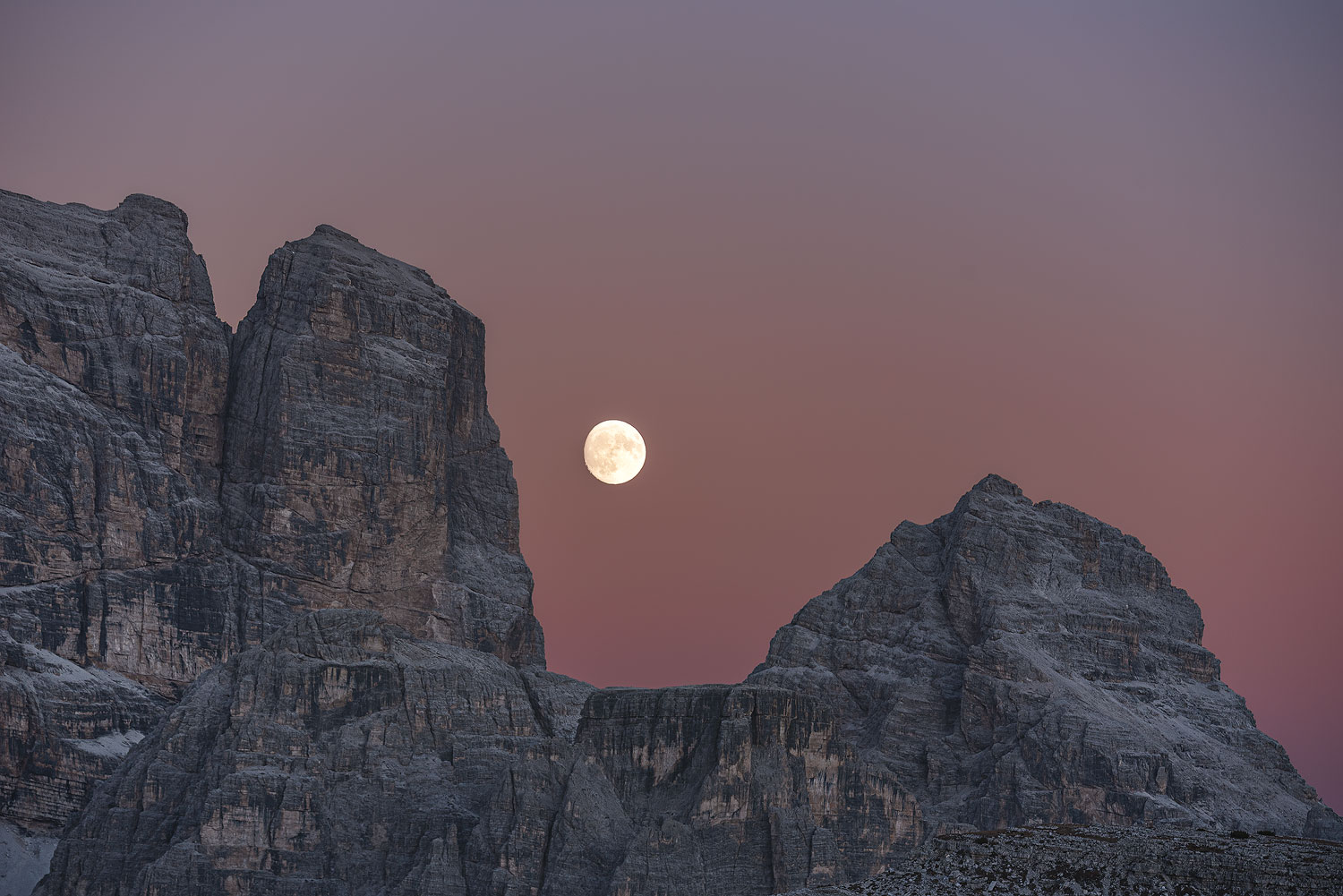 A close up to the Moon rising between two moutains in Dolomites