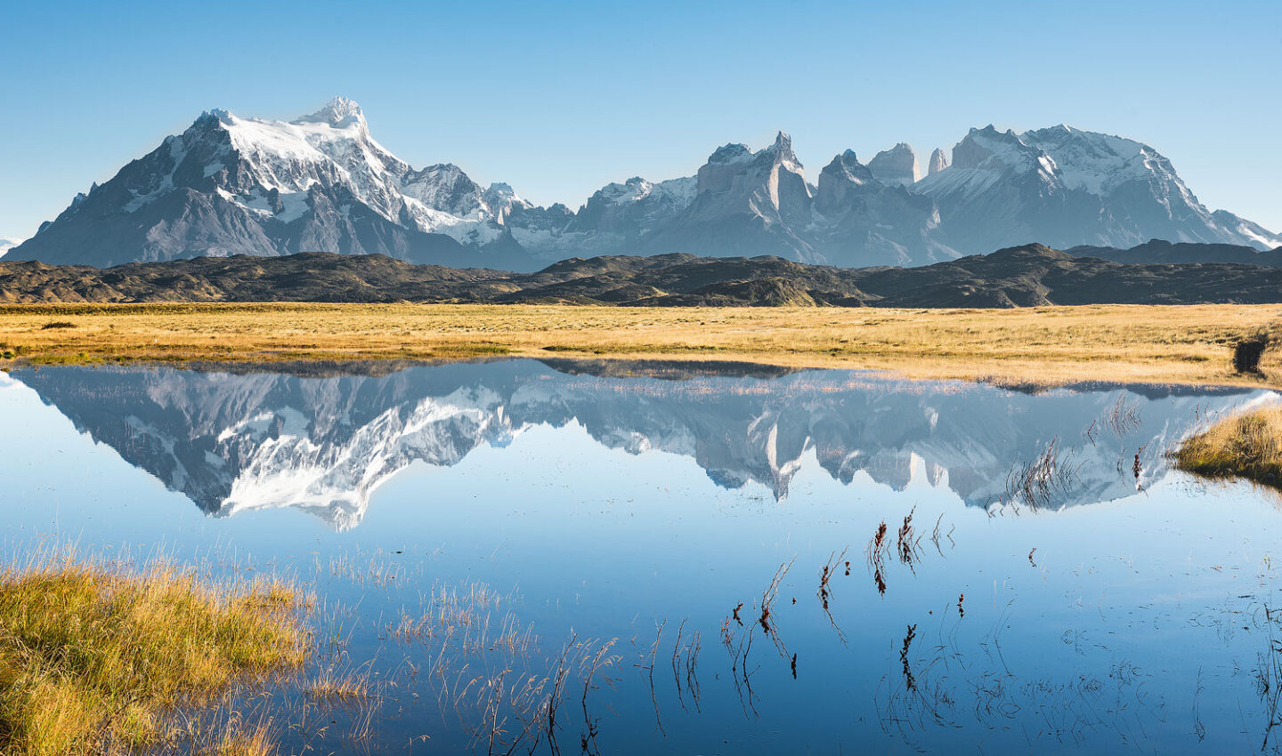 Perfect reflection of Torres del Paine mountain range on a clear sky Fall day