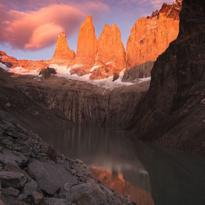 The first rays of the Sun painting with red color Las Torres del Paine at sunrise