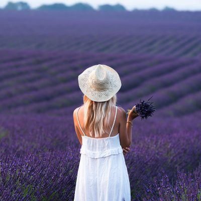 A woman with a bouquet of lavender in a lavender field. Model: lesdroners.fr