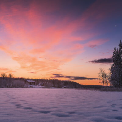 Sun rises above a small cabin along a frozen lake in Finnish Lapland